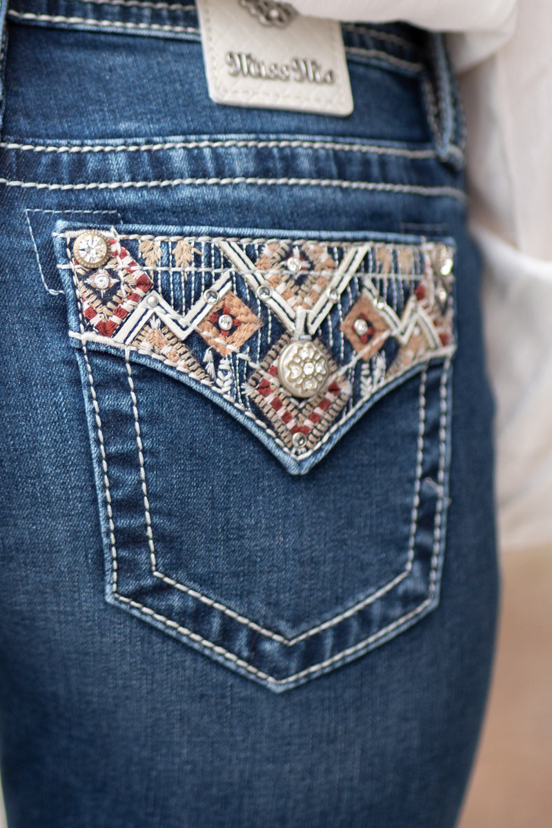 "Miss Me Collection: Fall 2020 Wash: Dark Wash Material: 66% Cotton 14% Lyocell 18% Polyester 2% Elastane Sequin Trim and Rhinestone Rivets  Mid Rise, 8.75"" Front Rise Embellished Aztec Embroidered Pocket Style #: M3649B2 Contact us for any additional measurements or sizing.  Haley wears a size small top, a 25 in jeans and a small in tops. She is wearing a size 25 in these jeans."