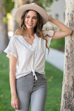 Hem & Thread   Light and easy, this knot top will be your go to for sunny days or to pair with a kimono.   Collection: Summer 2020 Color: Ivory White Neckline: V-Neck Sleeve: Flutter Sleeve 50% POLYESTER 50% COTTON CONTRAST 100% POLYESTER Style #: 7818F Contact us for any additional measurements or sizing.