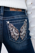 "Miss Me Collection: Fall 2020 Wash: Dark Wash Material:  Sequin Trim and Rhinestone Rivets  Mid Rise, 8.75"" Front Rise Embellished Floral Angel Wings Pockets  Style #: M3692S Get lost in this gorgeous pair of skinnies detailed with hand sanding, contrast stitching and embroidered floral inserts.  Contact us for any additional measurements or sizing."