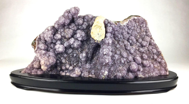 Amethyst mineral specimen on a wooden base