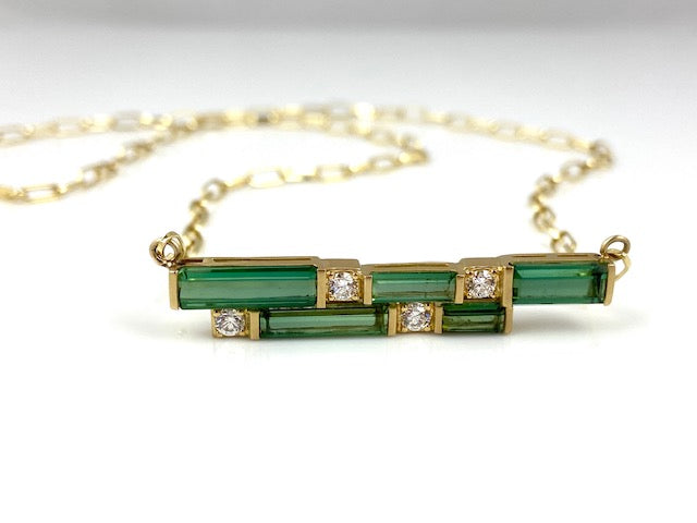 Stunning horizontal necklace center with emerald cut green tourmaline (4.49ctw) and white diamonds (0.36ctw) in 18k yellow gold.  On an 18k yellow gold chain, 20 inches in length.