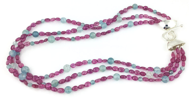 Smooth pink sapphire ovals and aquamarine spheres in a triple strand necklace with large hook clasp.