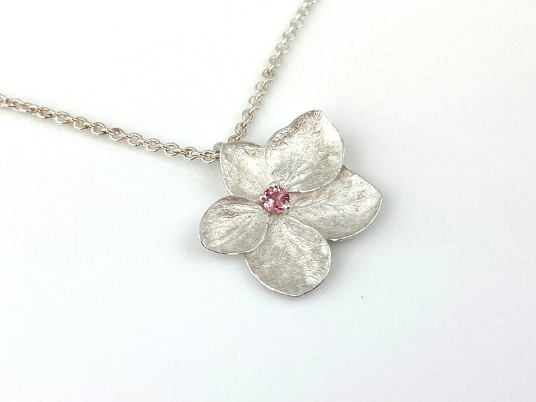 A pretty pink tourmaline centers this bright finish sterling silver 5-petal hydrangea necklace.  On adjustable 18 inch sterling silver chain.