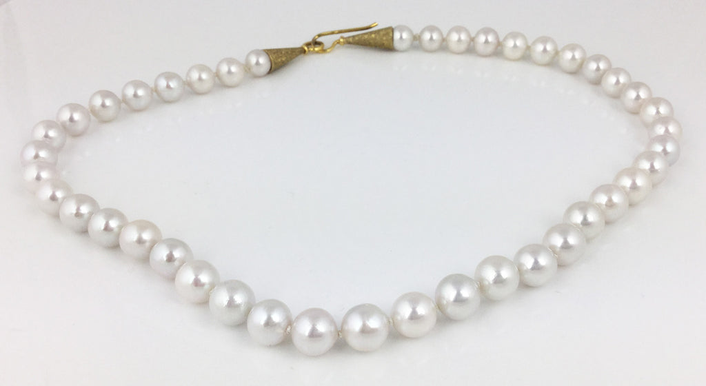hand knotted white bead nucleated cultured fresh water pearls with a stardust finish gold plated hook clasp.