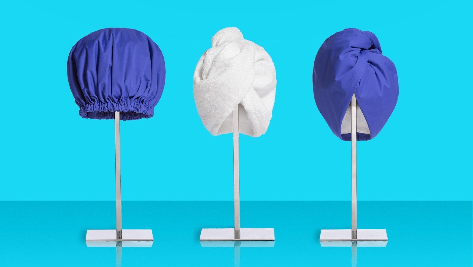 Turbella shower gear collection: 3 high performance luxury shower caps, hair-drying wrap and waterproof shower turban on blue pedestal