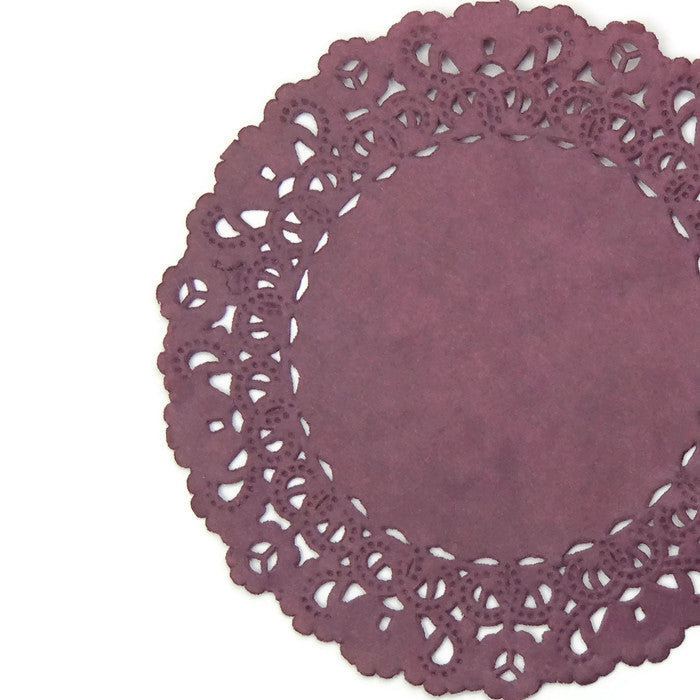 "Lacy, claret burgundy color paper doilies available in the Normandy style and in sizes ranging from 4"" to 16""."