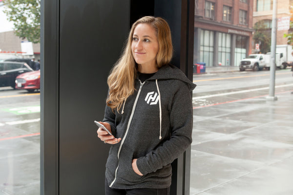 A woman wearing a dark gray zip-up hooded sweatshirt with drawstrings and the white HashiCorp H icon on her left chest.