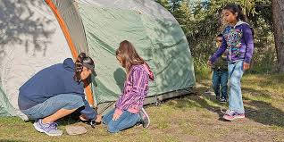 girl helping her mum set up a tent