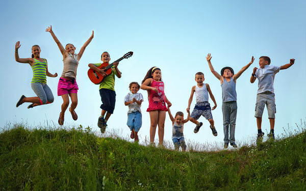 Camping Children Jumping Happily on a hill