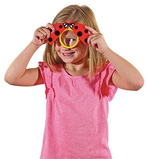 Girl looking through Ladybird Magnifier, children's magnifying toy for camping