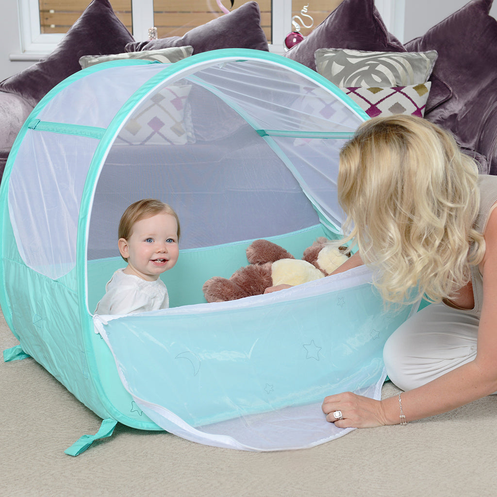 Baby in Pop-Up Travel Bubble Cot for camping babies, at Kids Camping Store, next to Mum