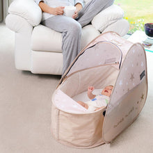 Load image into Gallery viewer, Pop Up Travel Cot with blackout cover, shown in a home