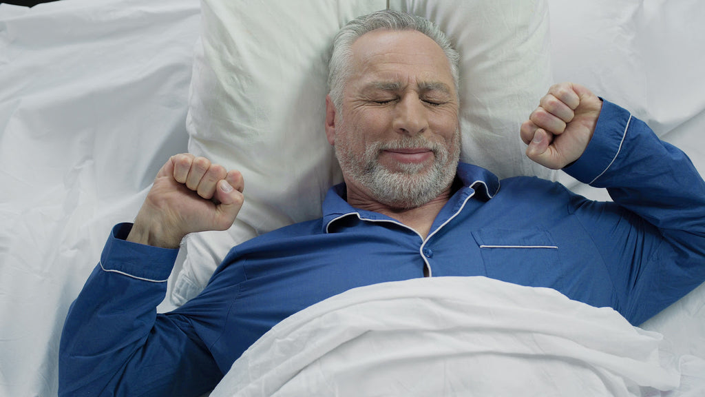 Happy senior man waking up in good mood after finding a healthy weight/sleep connection