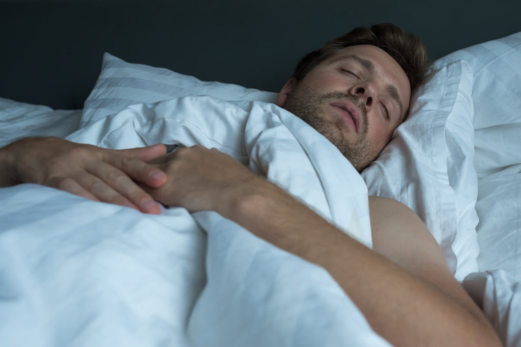 man sleeping receiving health benefits of sound sleep