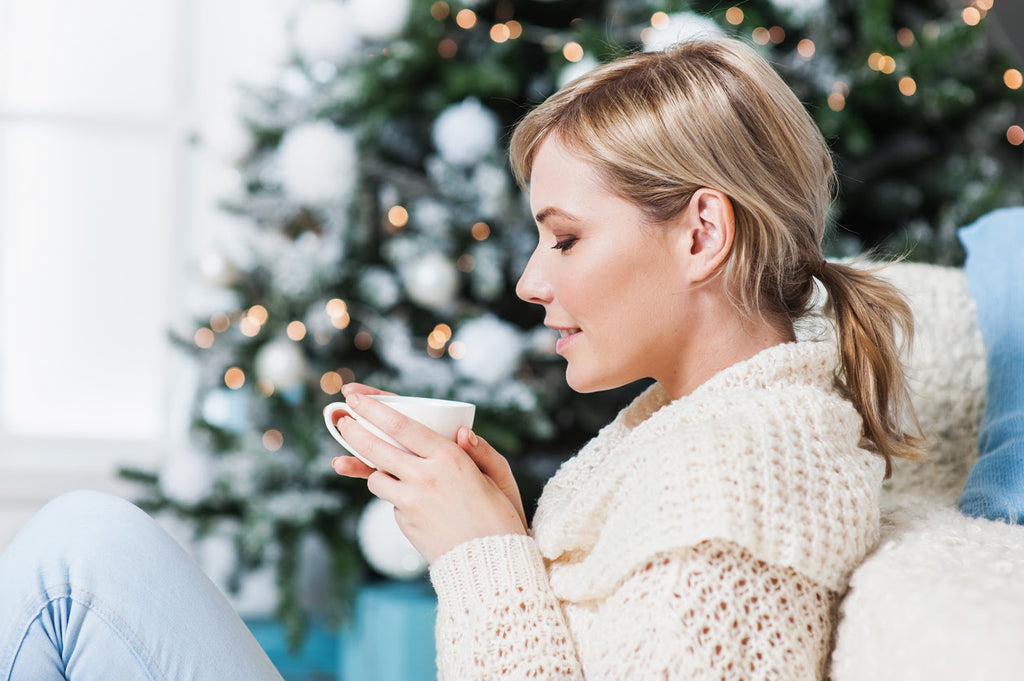 Young woman drinking tea and relaxing by the Christmas tree