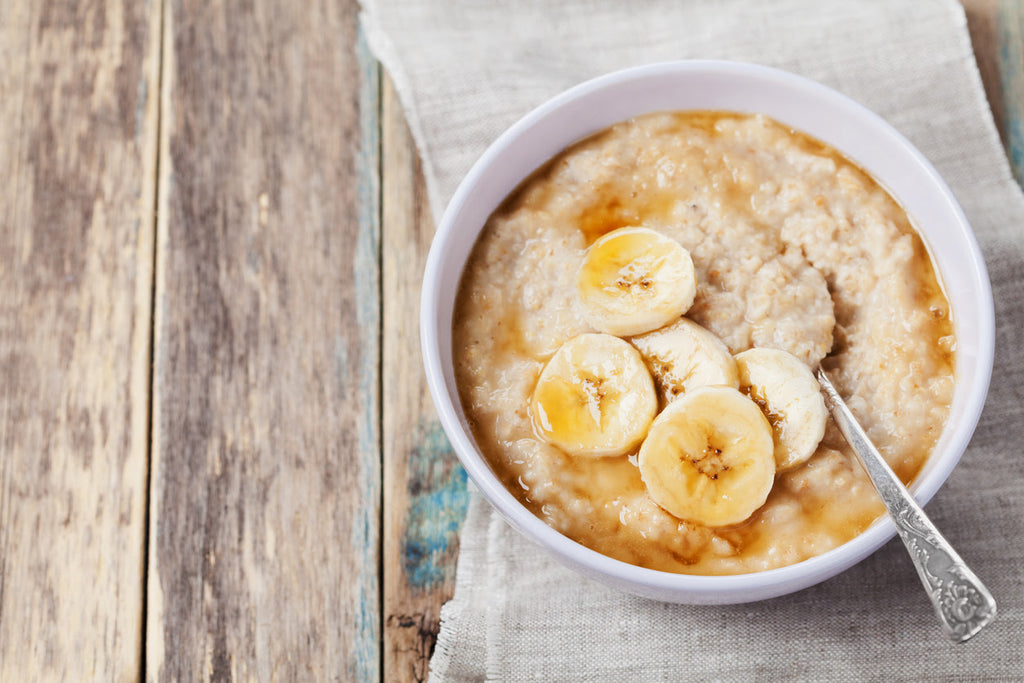 bowl of oatmeal with honey and bananas on wooden table