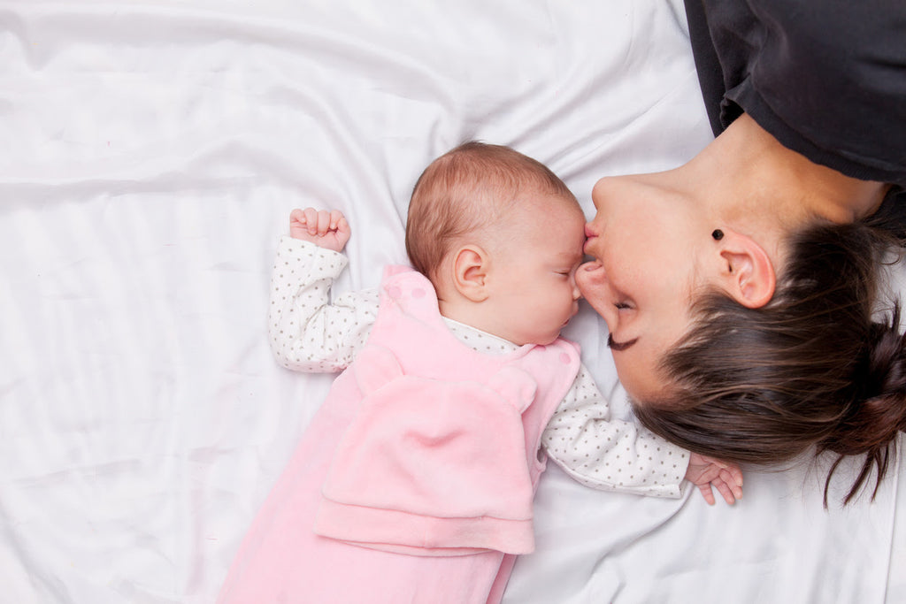 Happy mother and infant daughter on a new mattress