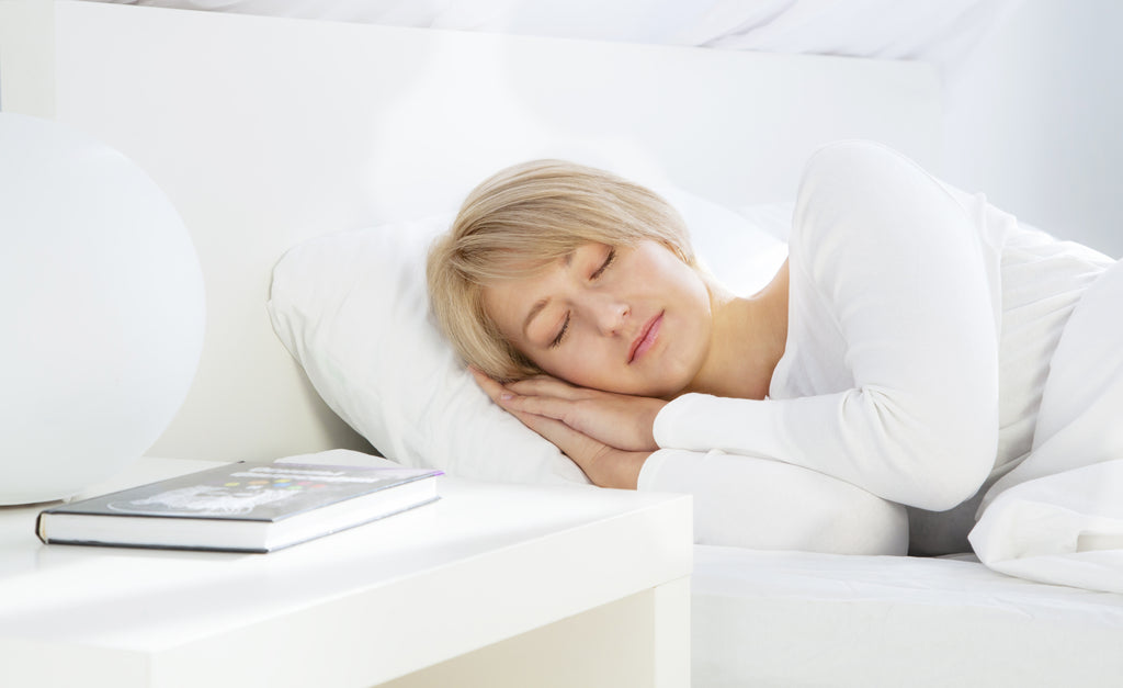 clean-room-sleeping-woman-white-bed-table-book