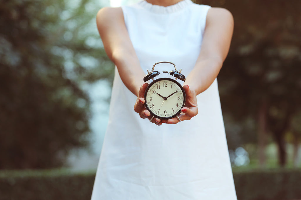 Woman holding out an alarm clock - resetting your body clock concept