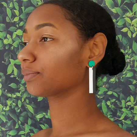 Model wearing geometric teal, white, and black color blocked statement earrings by the brand SCOTCHBONNET.