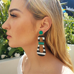 Model with blond hair wearing modern, curvy, black and white striped statement earrings with hand-beaded teal accents by the brand SCOTCHBONNET.