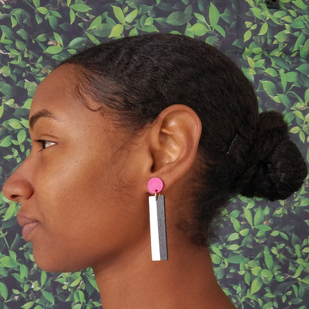 Model wearing geometric magenta, white, and black color blocked statement earrings by the brand SCOTCHBONNET.