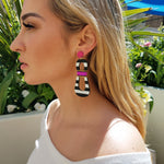 Blond model wearing modern, curvy, black and white striped statement earrings with hand-beaded magenta accents by the brand SCOTCHBONNET.