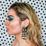 Model with teal eyeshadow wearing modern, curvy, black and white striped statement earrings with hand-beaded teal accents by the brand SCOTCHBONNET.