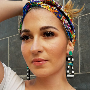 Model with colorful headband wearing modern, curvy, black and white striped statement earrings with hand-beaded teal accents by the brand SCOTCHBONNET.