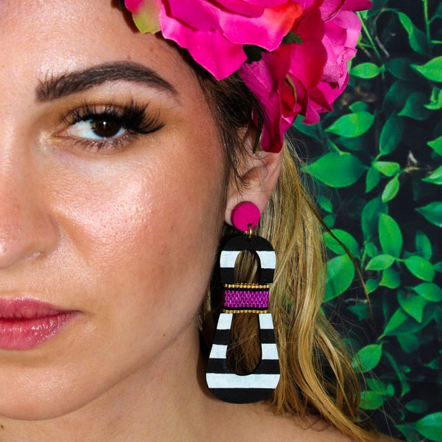 Model with floral crown wearing modern, curvy, black and white striped statement earrings with hand-beaded magenta accents by the brand SCOTCHBONNET.