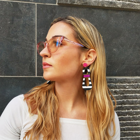 Model with magenta sunglasses wearing modern, curvy, black and white striped statement earrings with hand-beaded magenta accents by the brand SCOTCHBONNET.