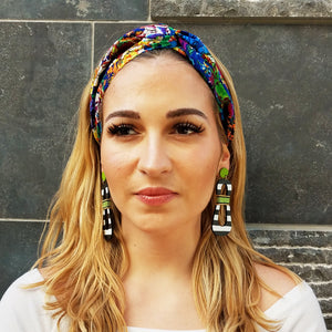 Model with colorful headband wearing modern, curvy, black and white striped statement earrings with hand-beaded chartreuse accents by the brand SCOTCHBONNET.
