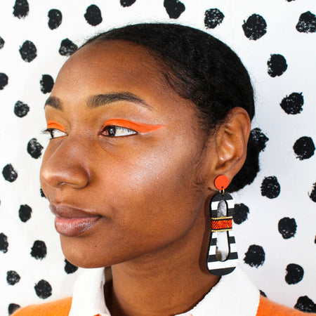 Model with orange eyeshadow wearing modern, curvy, black and white striped statement earrings with hand-beaded orange accents by the brand SCOTCHBONNET.