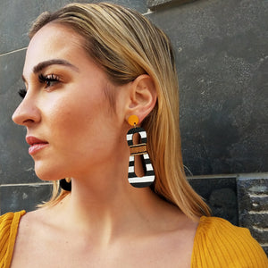 Side view of model wearing modern, curvy, black and white striped statement earrings with hand-beaded yellow accents by the brand SCOTCHBONNET.