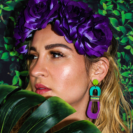 Model wearing modern, curvy, chartreuse, teal, and purple color blocked statement earrings with hand-beaded accents by the brand SCOTCHBONNET.