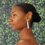 Model wearing geometric chartreuse, white, and black color blocked statement earrings by the brand SCOTCHBONNET.
