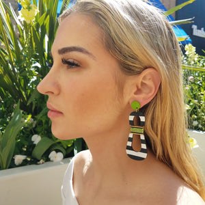 Model with blonde hair wearing modern, curvy, black and white striped statement earrings with hand-beaded chartreuse accents by the brand SCOTCHBONNET.