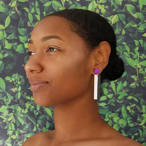 Model wearing geometric purple, white, and black color blocked statement earrings by the brand SCOTCHBONNET.