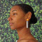 Model wearing geometric yellow, white, and black color blocked statement earrings by the brand SCOTCHBONNET.