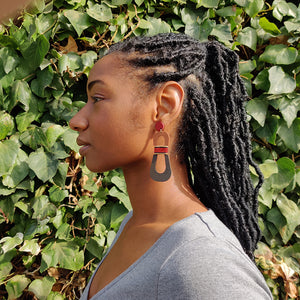 Model wearing modern, curvy, red, brown, and dark brown color blocked statement earrings with hand-beaded accents by the brand SCOTCHBONNET.