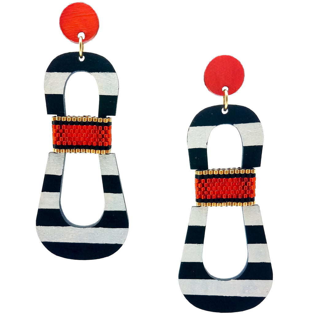 Modern, curvy, black and white striped statement earrings with hand-beaded orange accents by the brand SCOTCHBONNET.