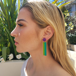 Model with blonde hair wearing geometric color blocked statement earrings in bright shades of purple, green and teal by the brand SCOTCHBONNET.