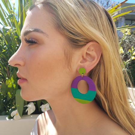 Model with blonde hair wearing large, round, chartreuse, teal and purple color blocked neutral tone statement earrings by the brand SCOTCHBONNET.