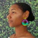 Model wearing large, round, chartreuse, teal and purple color blocked neutral tone statement earrings by the brand SCOTCHBONNET.