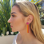 Model with blonde hair wearing geometric color blocked statement earrings in bright shades of magenta, orange and yellow by the brand SCOTCHBONNET.