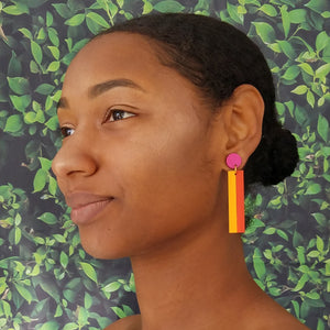 Model with dark hair wearing geometric color blocked statement earrings in bright shades of magenta, orange and yellow by the brand SCOTCHBONNET.
