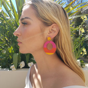Side view of model wearing large, round, yellow, magenta and orange color blocked neutral tone statement earrings by the brand SCOTCHBONNET.