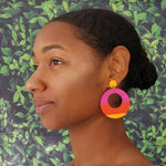 Model wearing large, round, yellow, magenta and orange color blocked neutral tone statement earrings by the brand SCOTCHBONNET.