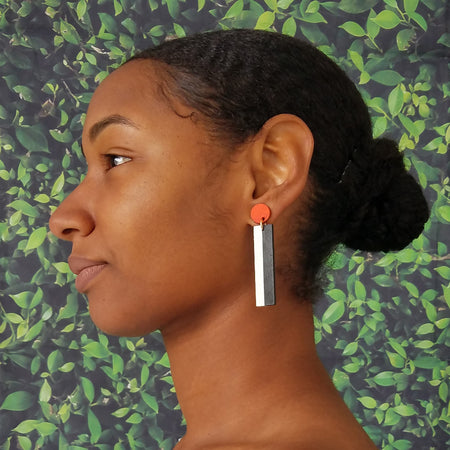 Model wearing geometric orange, white, and black color blocked statement earrings by the brand SCOTCHBONNET.