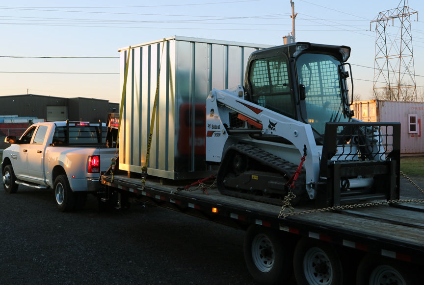 Container placement using a Bobcat or forklift.